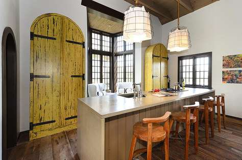 Kitchen features a pair of custom crafted, freestanding arched cabinets made from old cypress