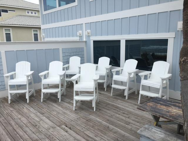 White rockers and tall beach chairs on back deck