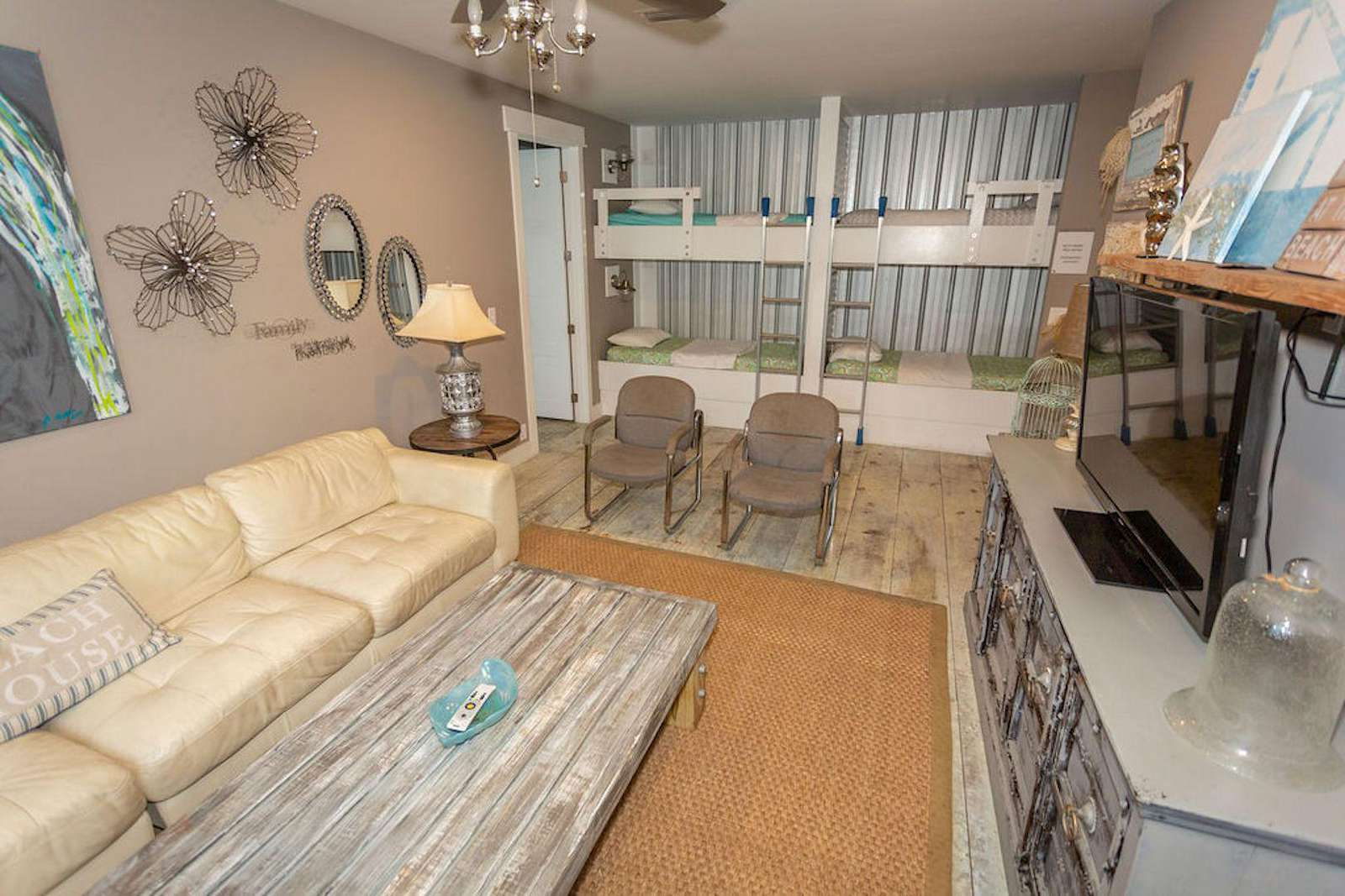 upstairs family room with large sectional, flat screen and 2 sets of bunks