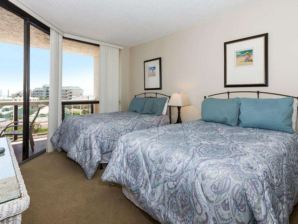 The second bedroom features 2 queen sized beds and access to the balcony.