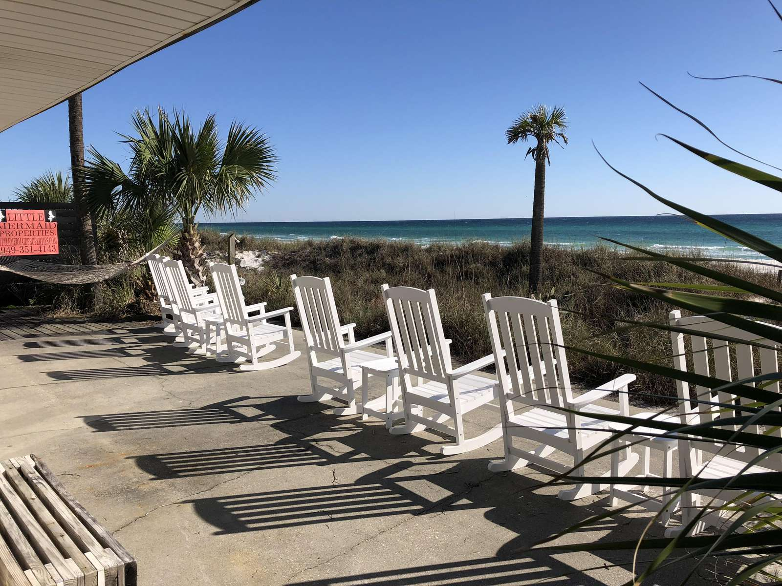 8 Rocking chairs facing gulf--large sun screen overhead