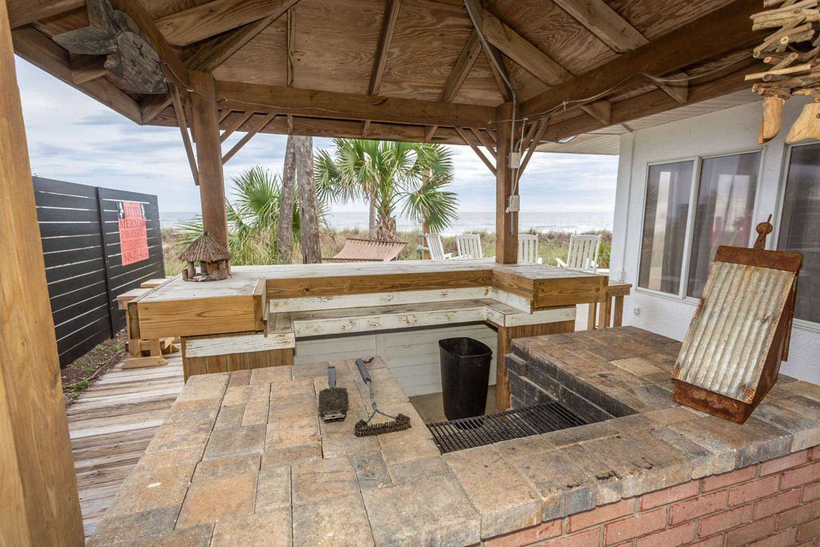 Custom barbecue with built in grill and large serving table, barstools, bar, overlooking gulf