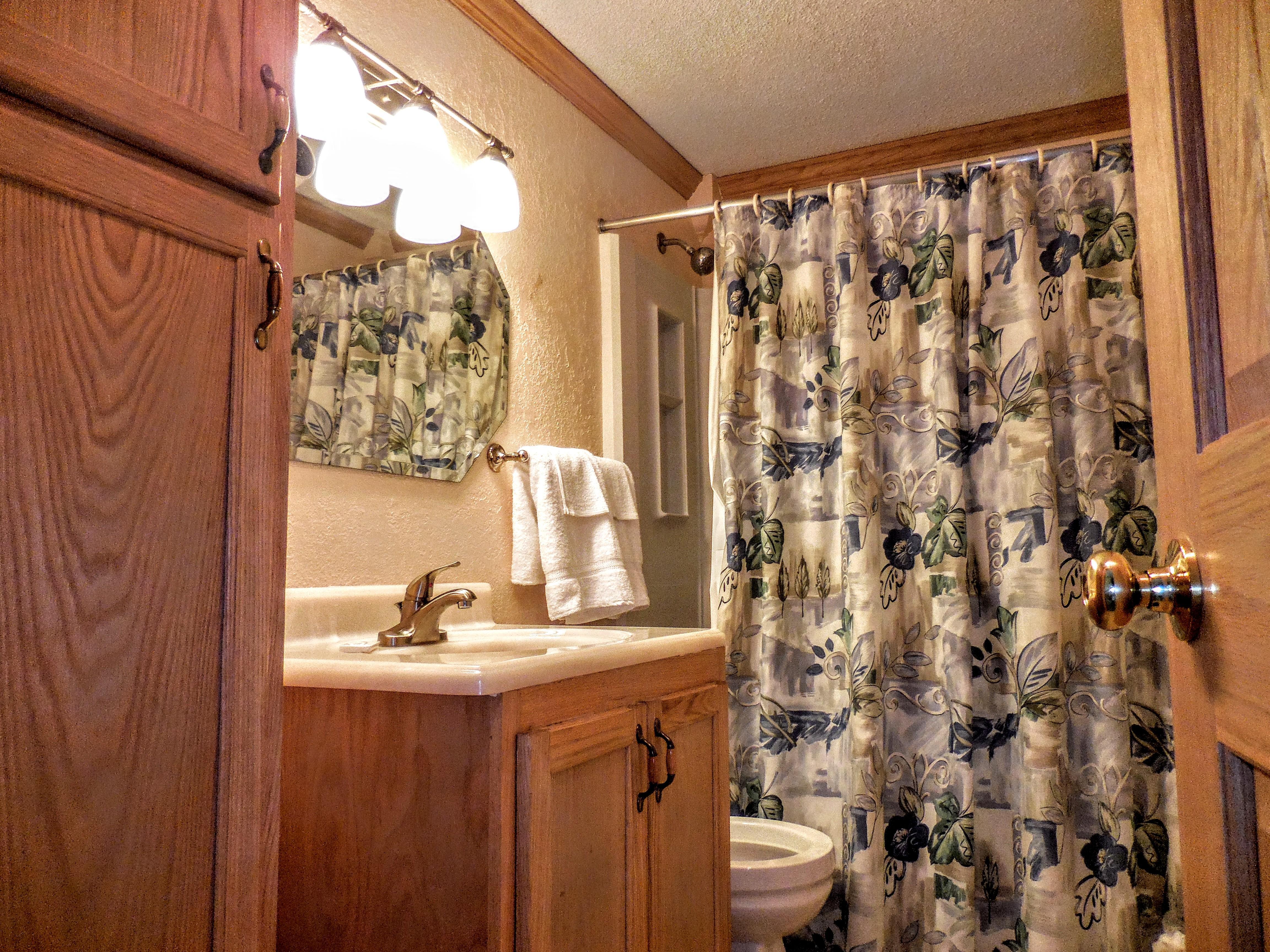 Hallway bathroom includes tub and shower
