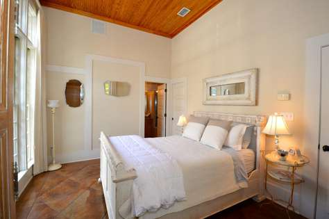 First Floor Guest Bedroom with private bath. Large floor to ceiling windows and beautiful stained floors and wood ceiling