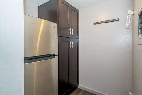 Walk-in closet has the refrigerator/freezer and cupboards for storage (behind kitchen)