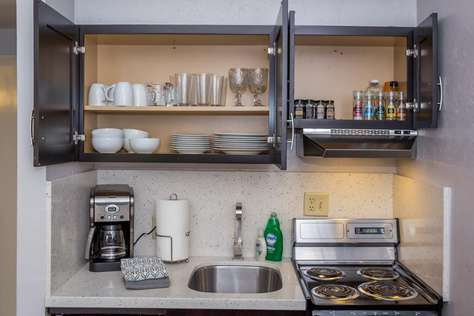 Cupboards are stocked with dishes, pots and pans, utensils, spices and cooking oils.