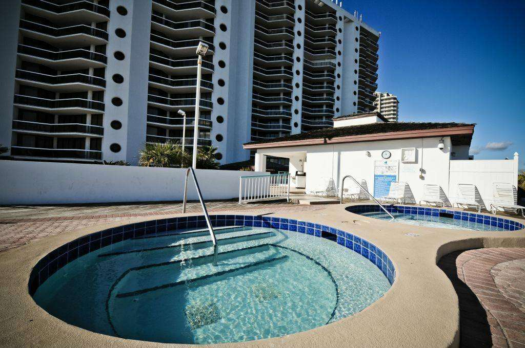 The pool deck features 2 hot tubs, kiddie pool, a large pool, and a tiki bar.