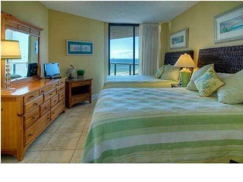 The second bedroom features 2 queen sized beds and balcony access.