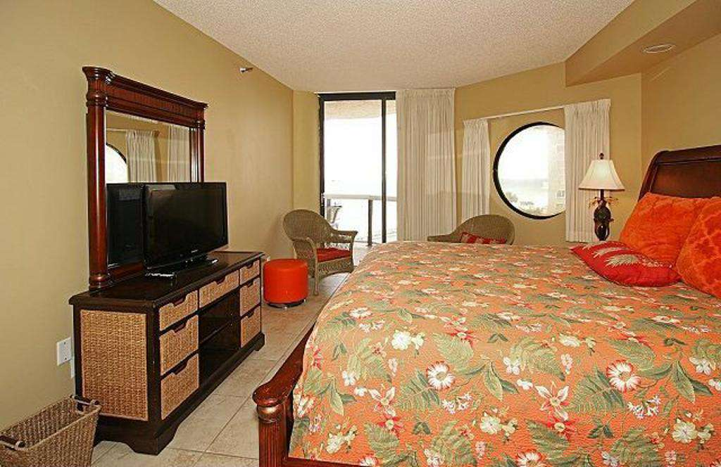 The master bedroom features a king sized bed, en suite bathroom, and balcony access with gorgeous ocean views!