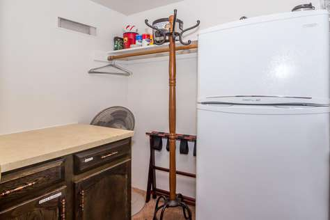 The refrigerator is in the walk-in closet behind kitchen.