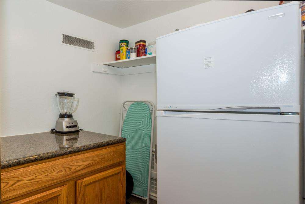 Walk-in closet behind kitchen w/refrigerator and ironing board.
