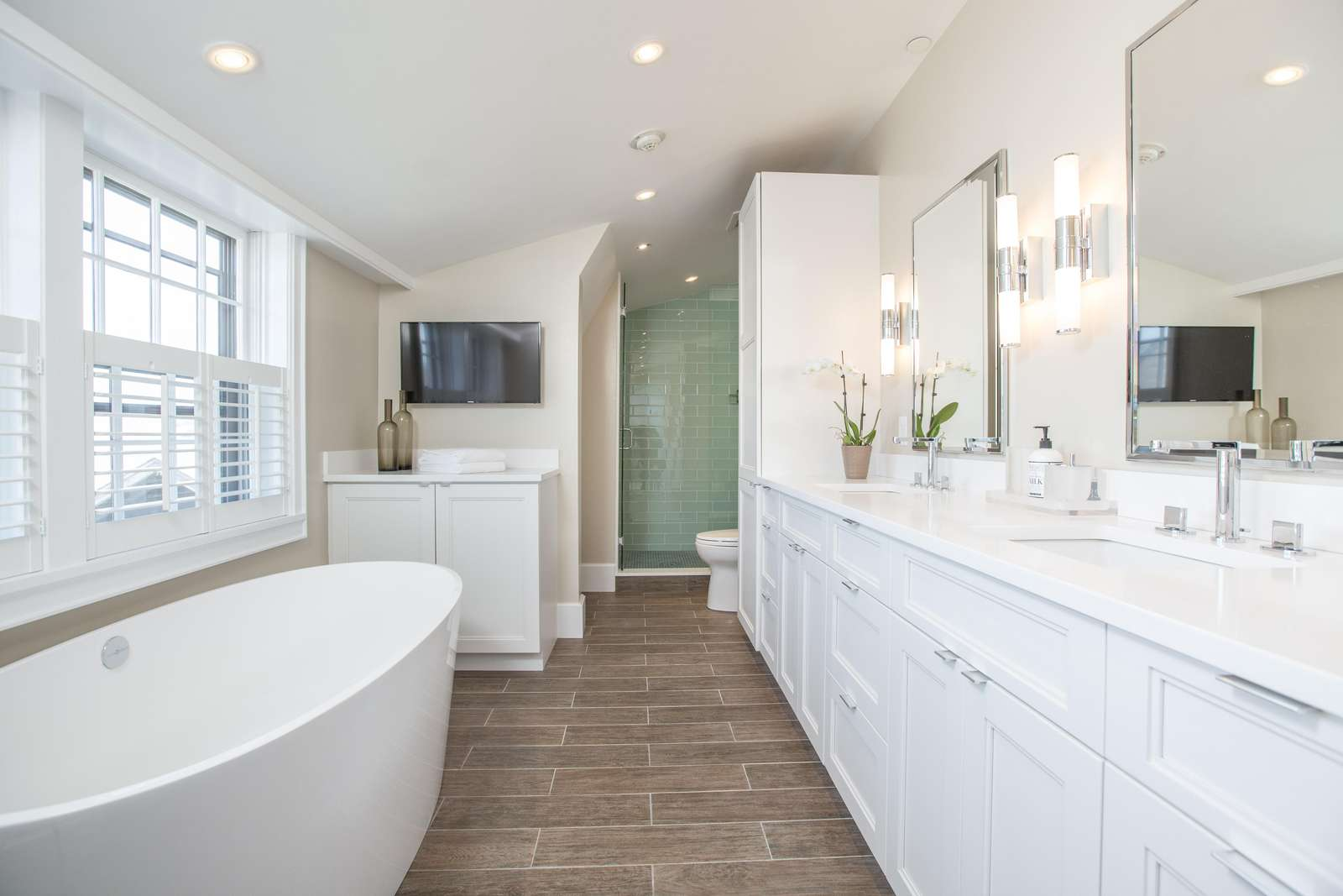 Master bathroom with dual vanity, tub, LED TV and elegant tiled shower