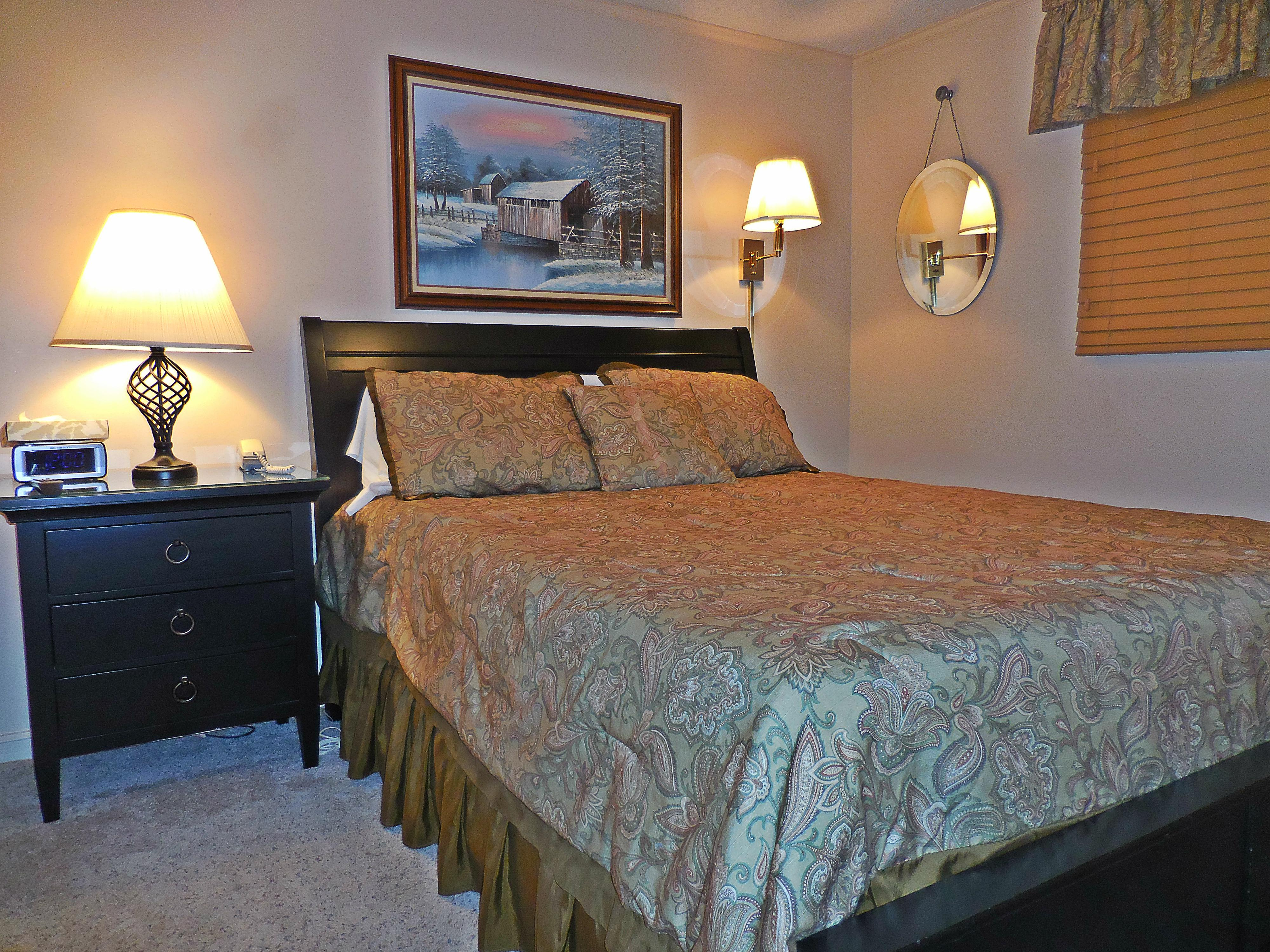 Queen-sized be in bedroom with flatscreen TV on wall