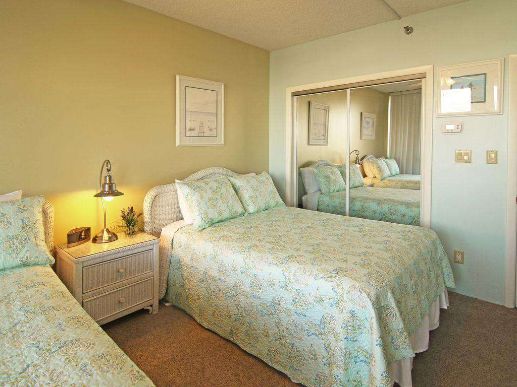 The second bedroom features 2 full sized beds and a bathroom directly next to it.