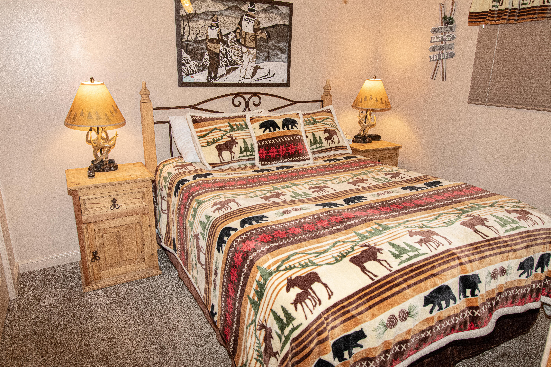 Queen size bed, TV, & ceiling fan in comfy bedroom