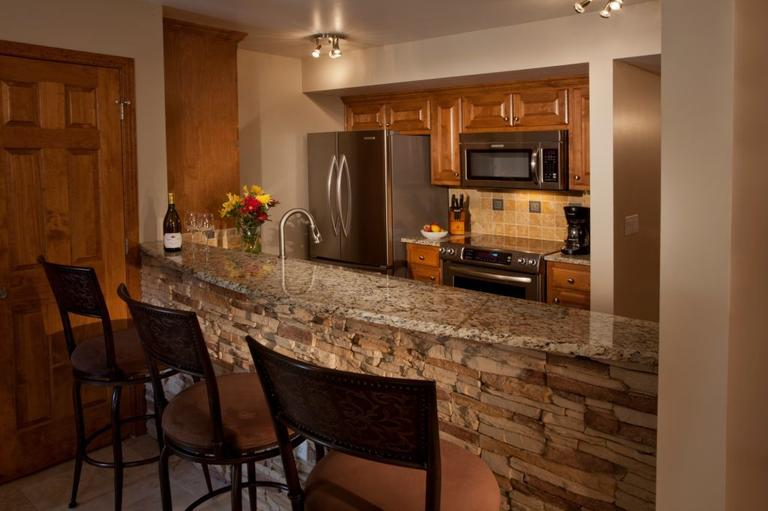 Kitchen with bar seating. It is inviting and is comfortable to work in.