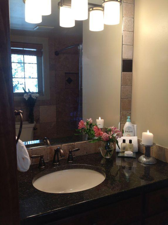 Master bathroom with granite counter, tiled bath, and hair dryer.