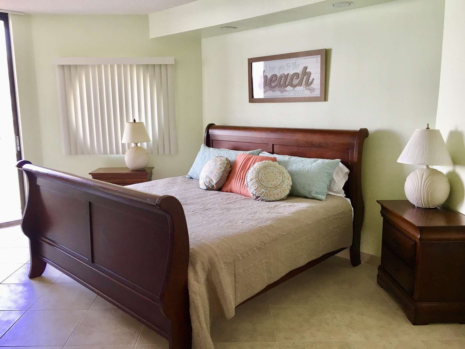 The master bedroom also features an en-suite bathroom, balcony access with a view of the Gulf, and a large closet.