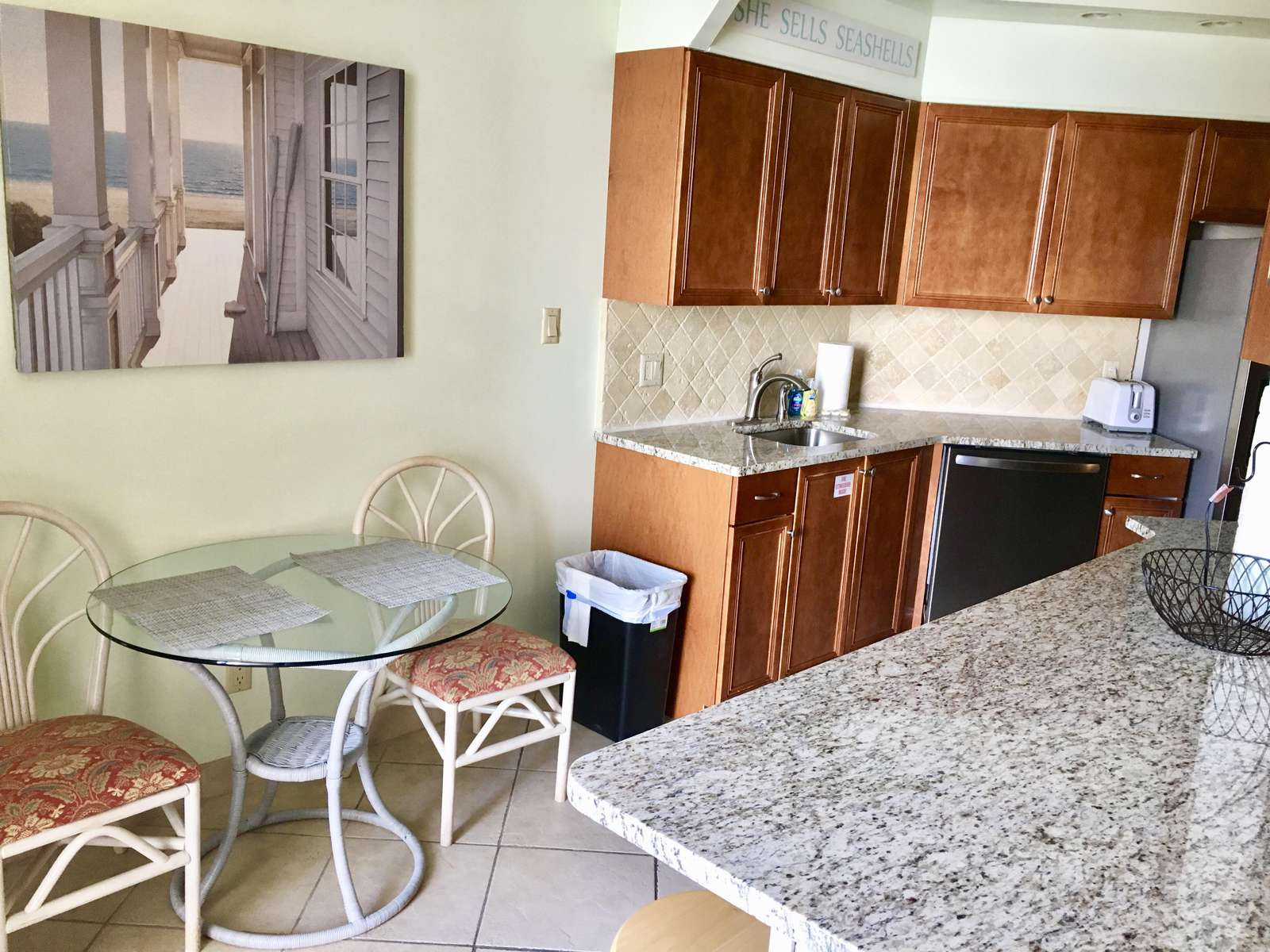The kitchen flows into the living room with an eat-in bar area and balcony access.