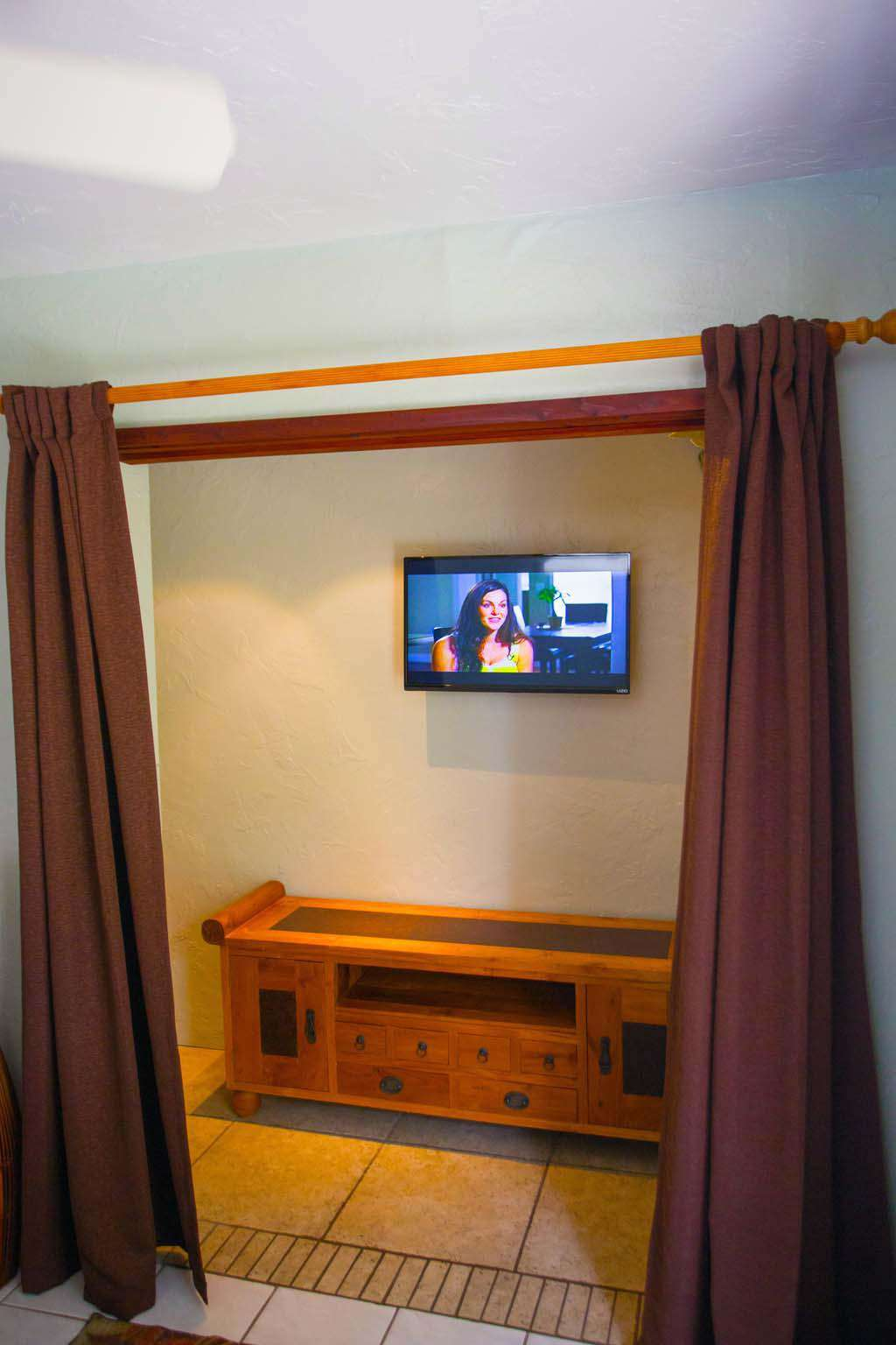 Flat screen smart TV iomn front of king size bed