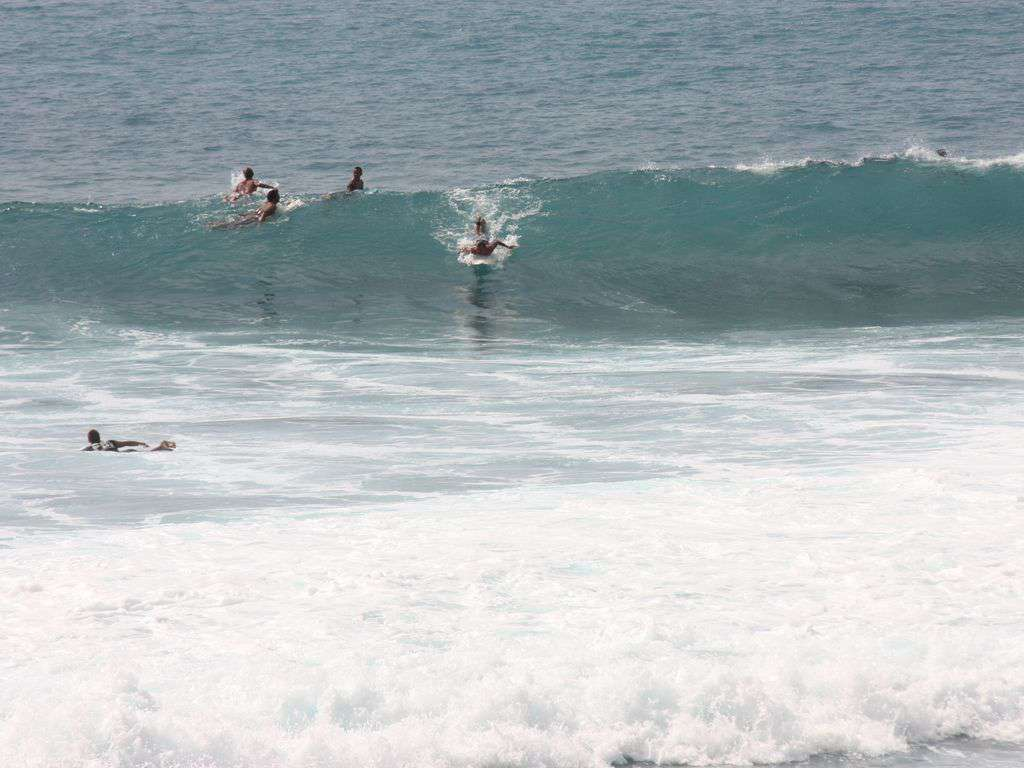 """Surfers delight at the popular """"Banyans"""" surf spot."""