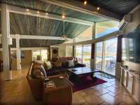 The living room with the relaxing waterfront deck in the background. thumb