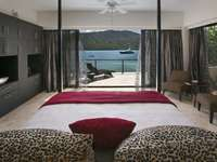 Many luxurious bedrooms with private balconies and rejuvenating water views! thumb