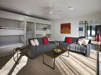 Four bunk beds and a comfortable lounge and seating area thumb