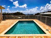 The spacious pool deck with grill, and covered seating area (to left of frame). thumb