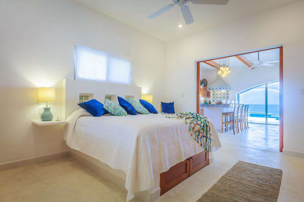 King Bed, with views out of doors, through living area to the Caribbean