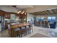 The gourmet kitchen with custom cabinetry, tiled-countertops, and a center island thumb