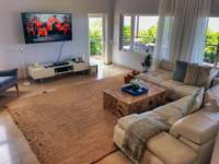 Great room with modern furnishings and vaulted ceilings thumb