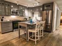 The open kitchen equipped with stainless-steel appliances thumb