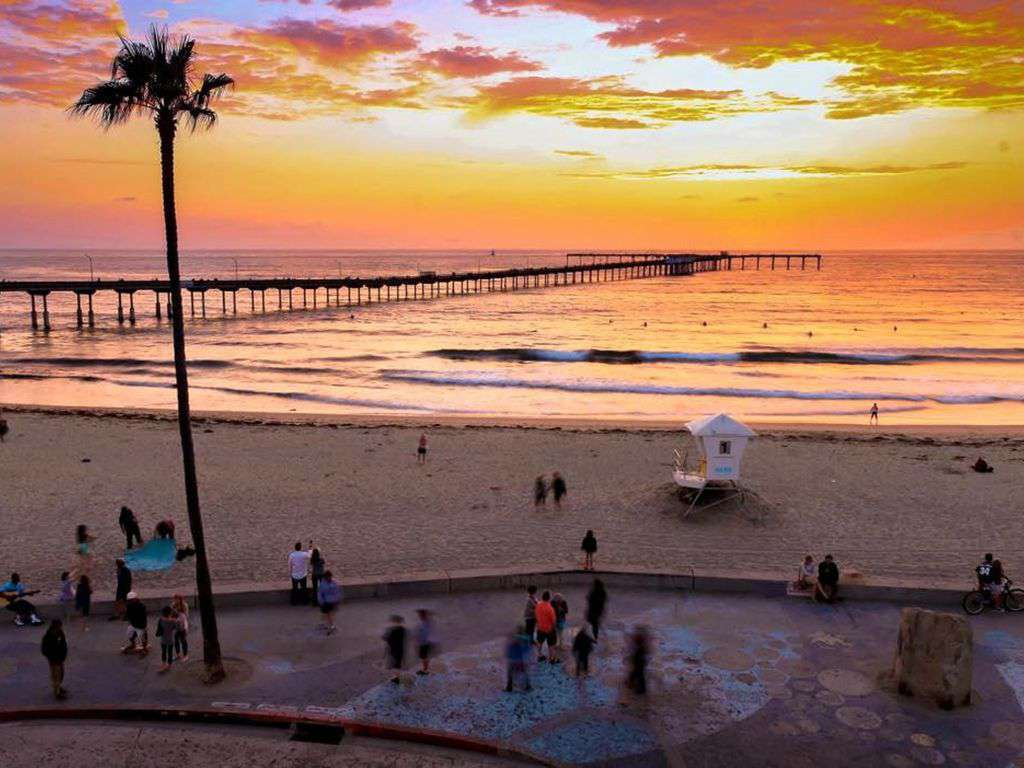 Public beach offers swimming, surfing, lifeguards, restrooms, showers, and pier.