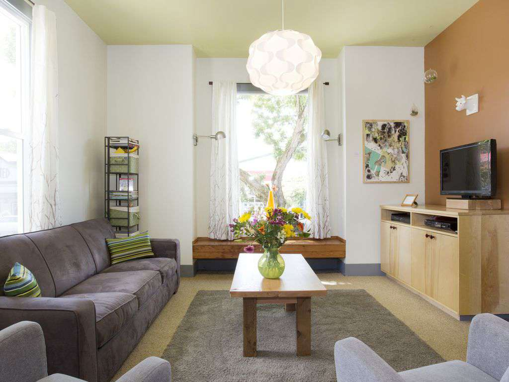 The living room of the upper unit has a large couch and various chairs to sit in.