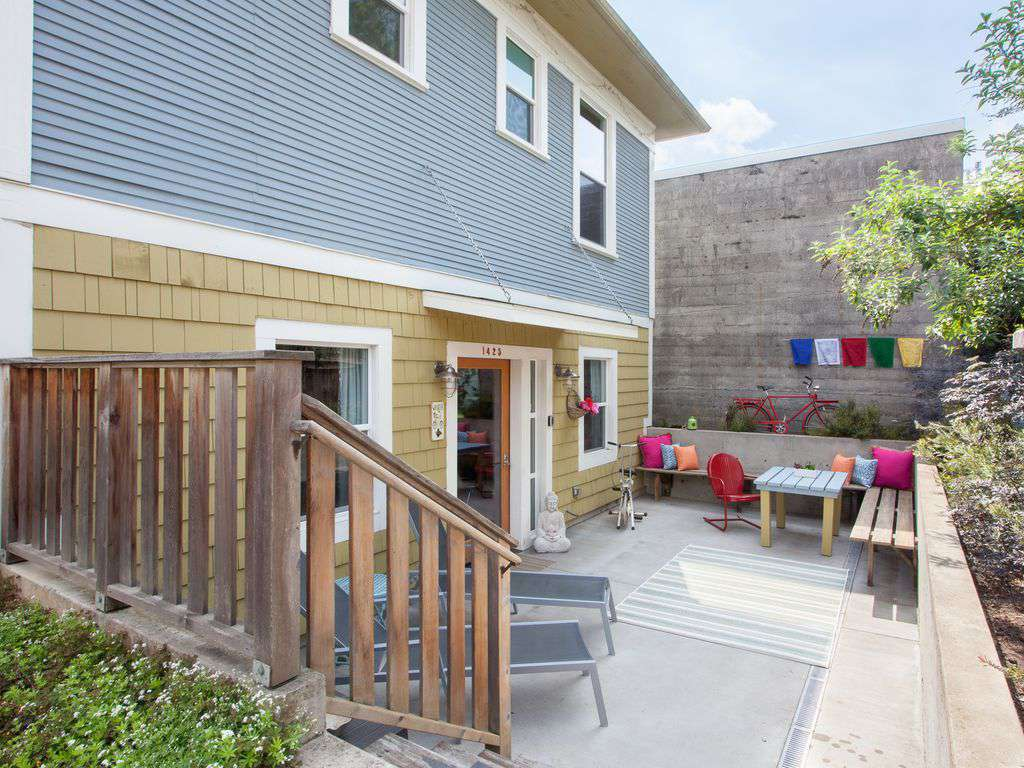 Entrance to the lower unit is behind the house and down a few stairs with a lovely patio.