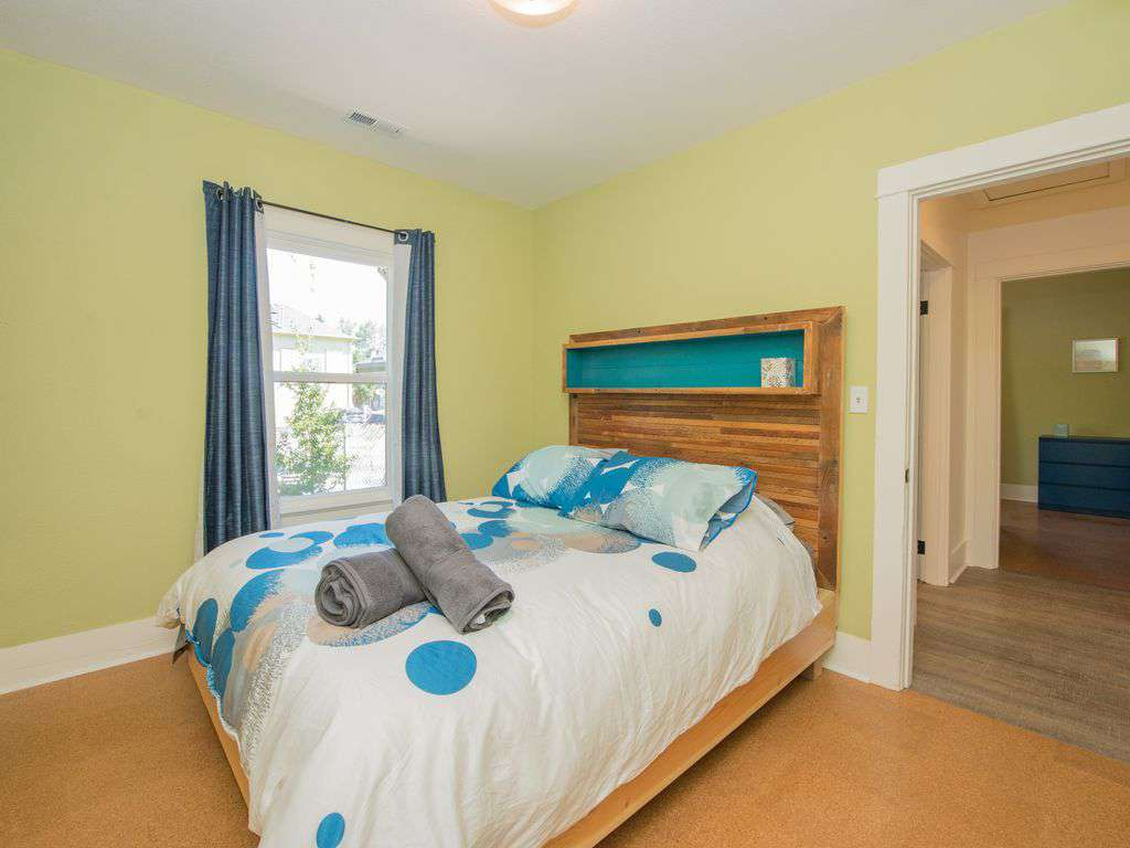 The main floor has 2 bedrooms, this one has a queen bed with custom headboard.
