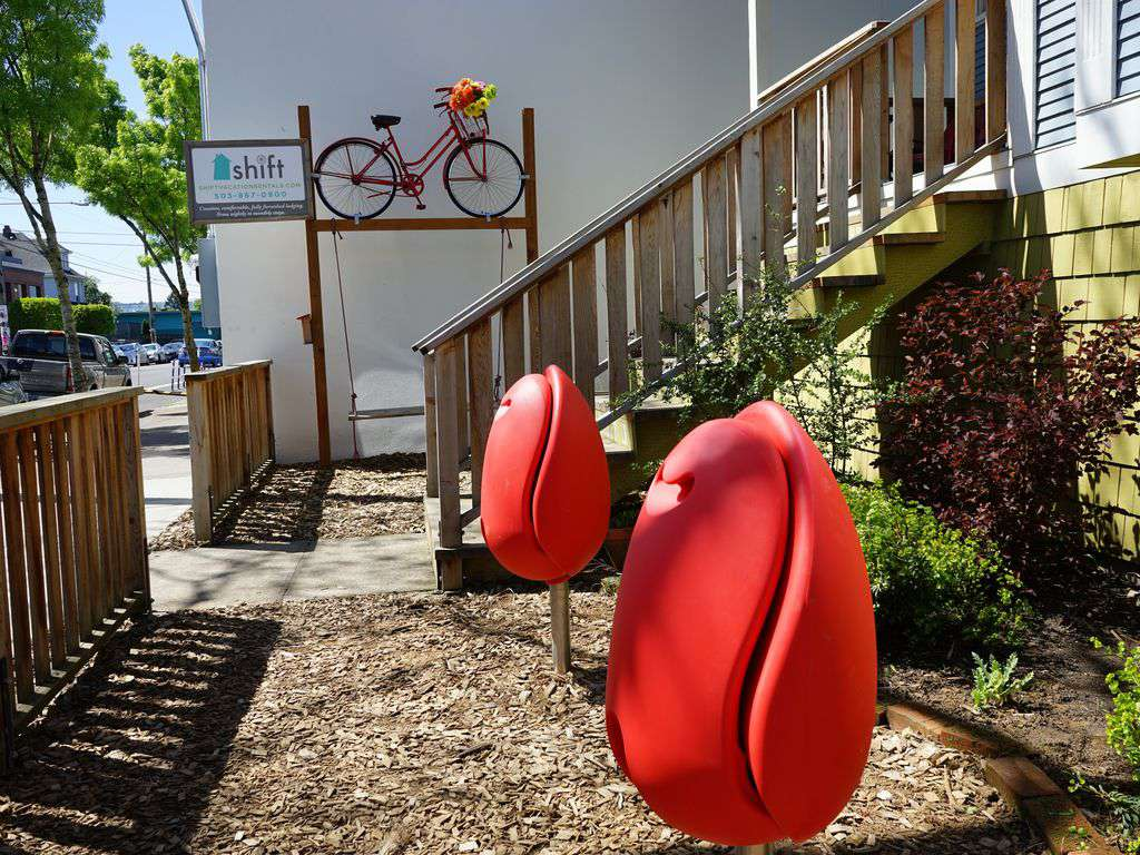 The outside is adorned with tulip chairs, and swings under the bike!