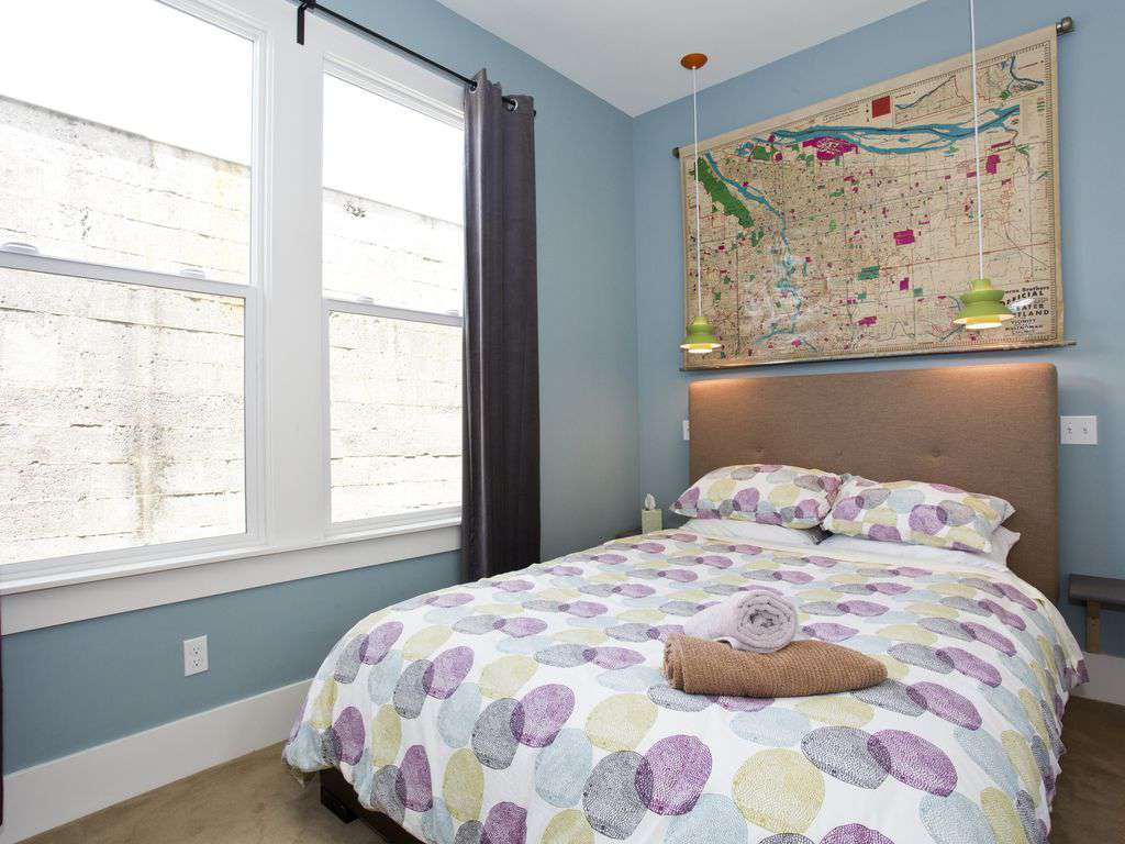 Bedroom on first floor with queen mattress and historic Portland map.