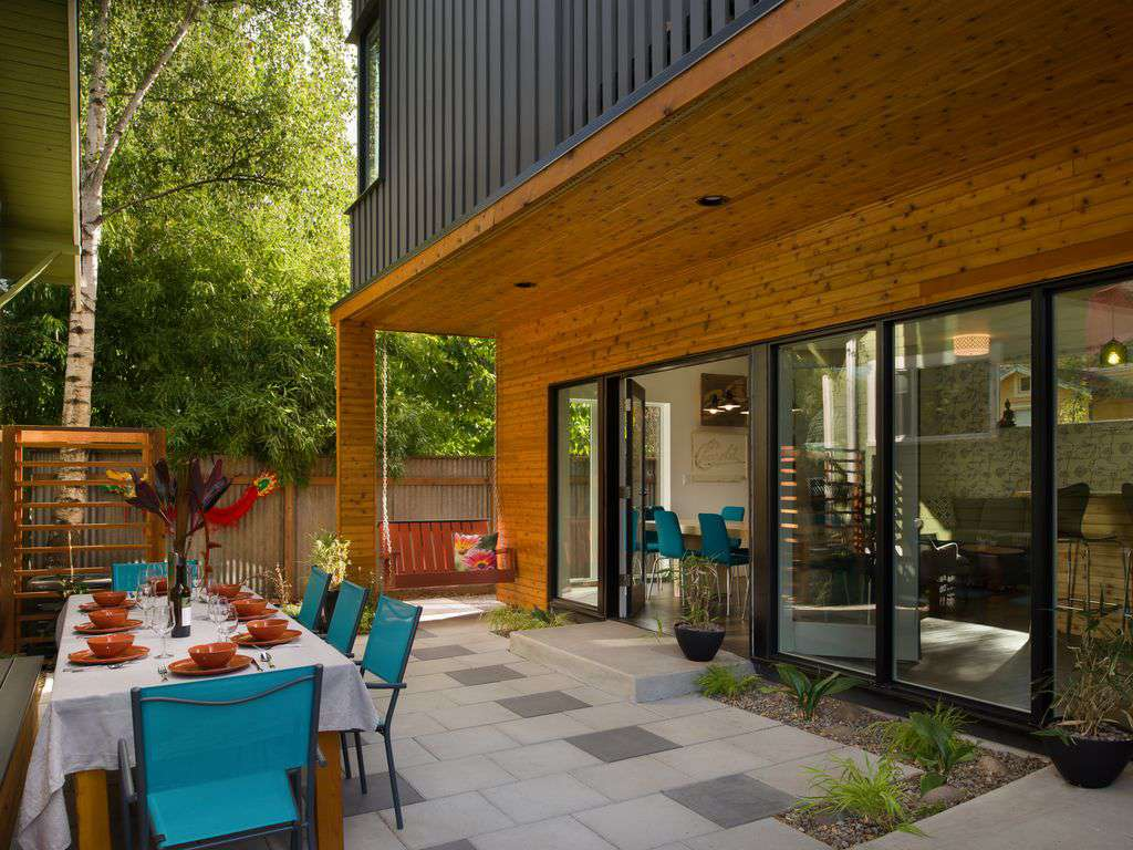An amazing back patio with large table, sweet swing, and beautiful plants.