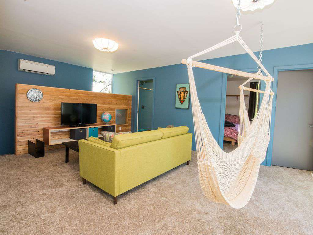 The upstairs boasts another hang out space with TV, games, and cool hammocks.