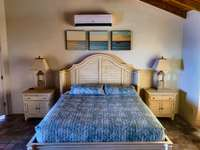 Bedroom 4 (main level) with en-suite bath and adjoining porch overlooking pool area and ocean view! thumb