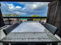 The deck with outdoor seating and fantastic views of Sapphire Beach! thumb