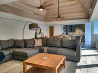 The comfortably furnished living room with high ceilings thumb
