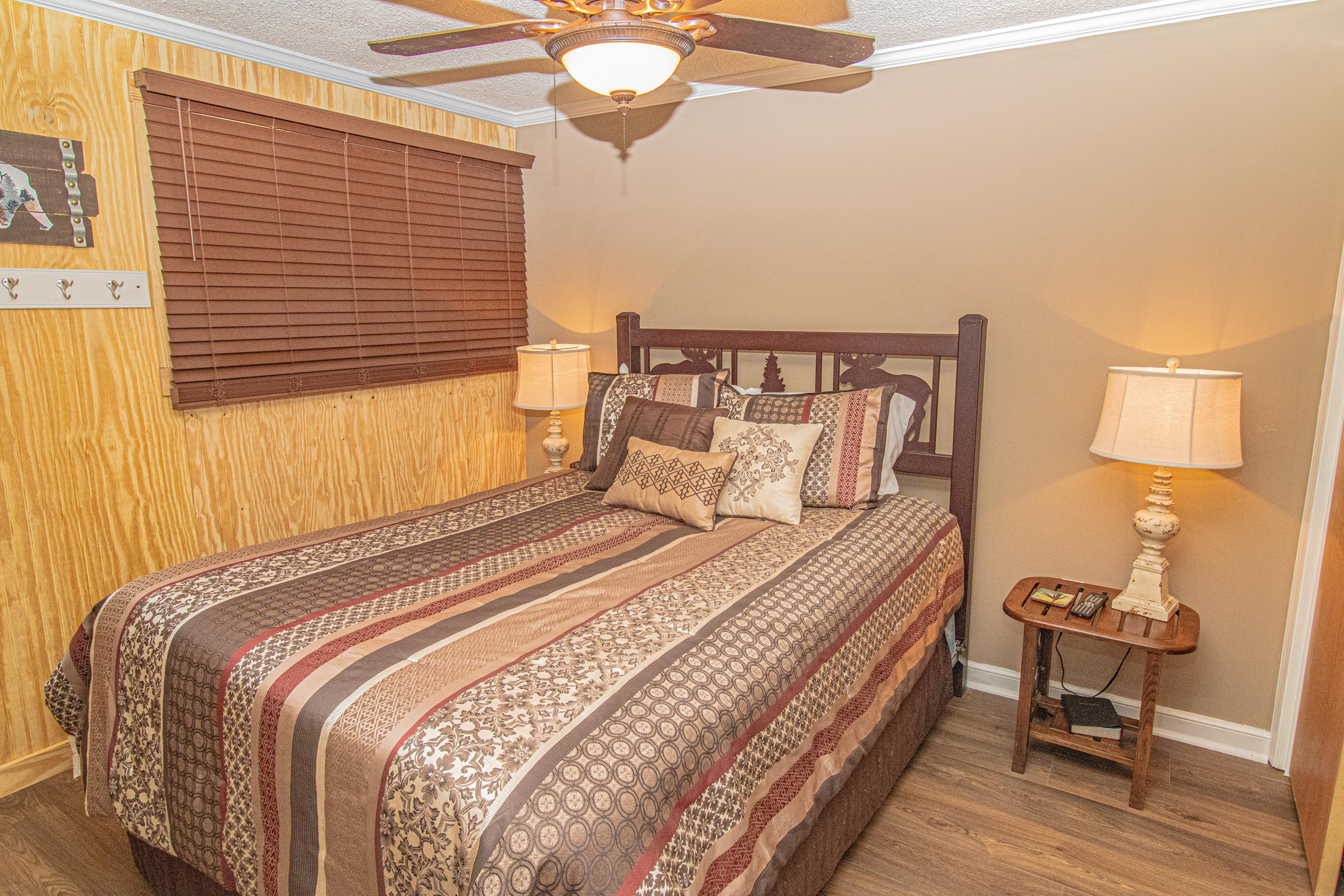 Second bedroom features queen-sized bed and wall-mounted TV