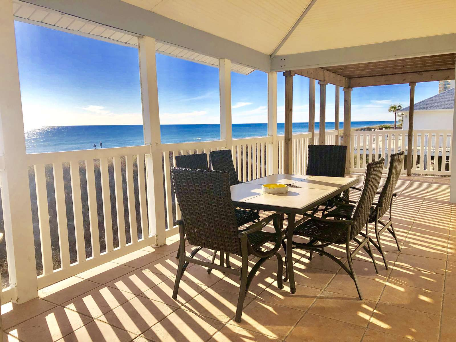 Back deck overlooking gulf with tables, chairs, grills, beach toys