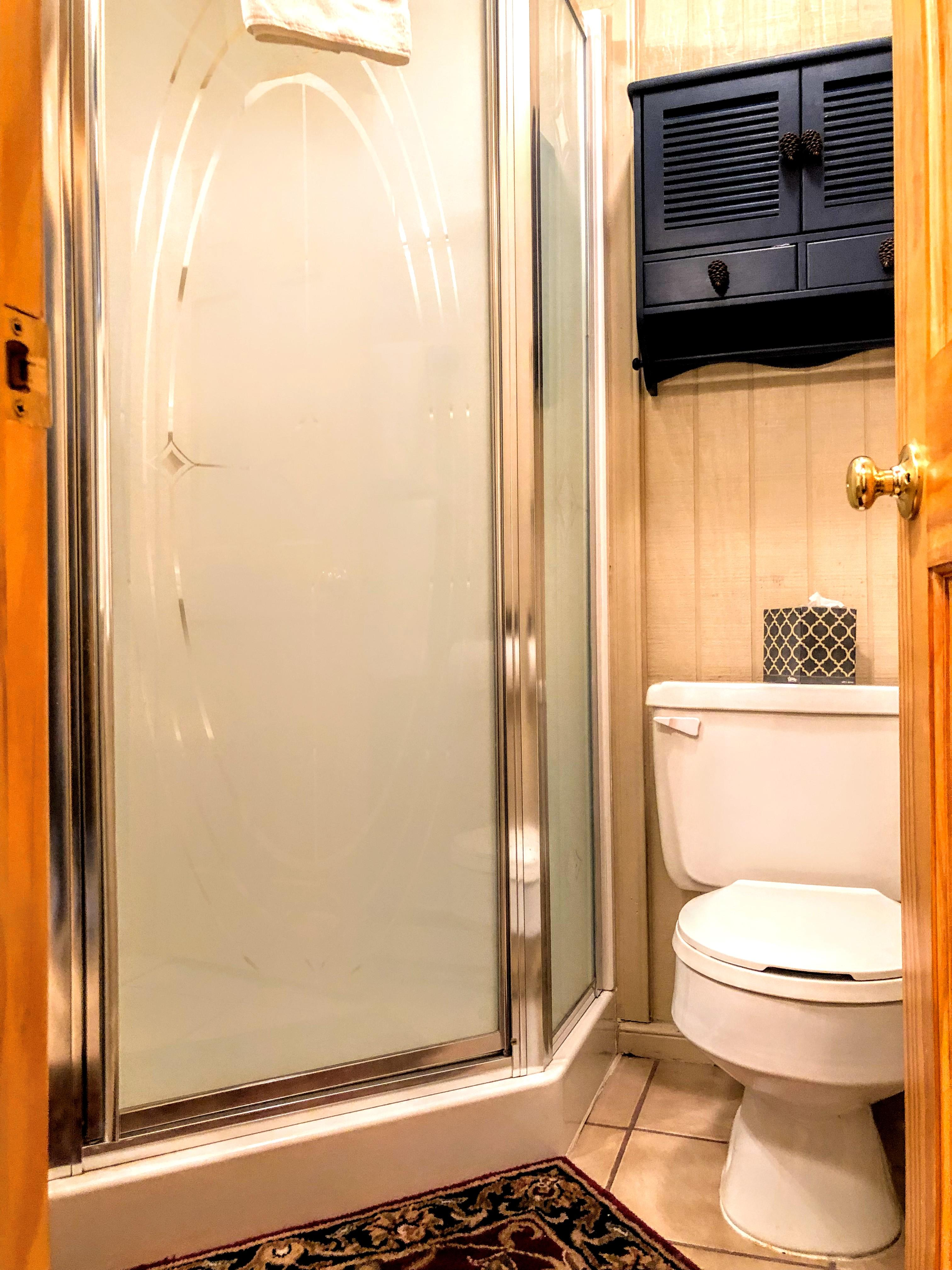 Full second bathroom in hallway next to second bedroom; has a shower enclosure.
