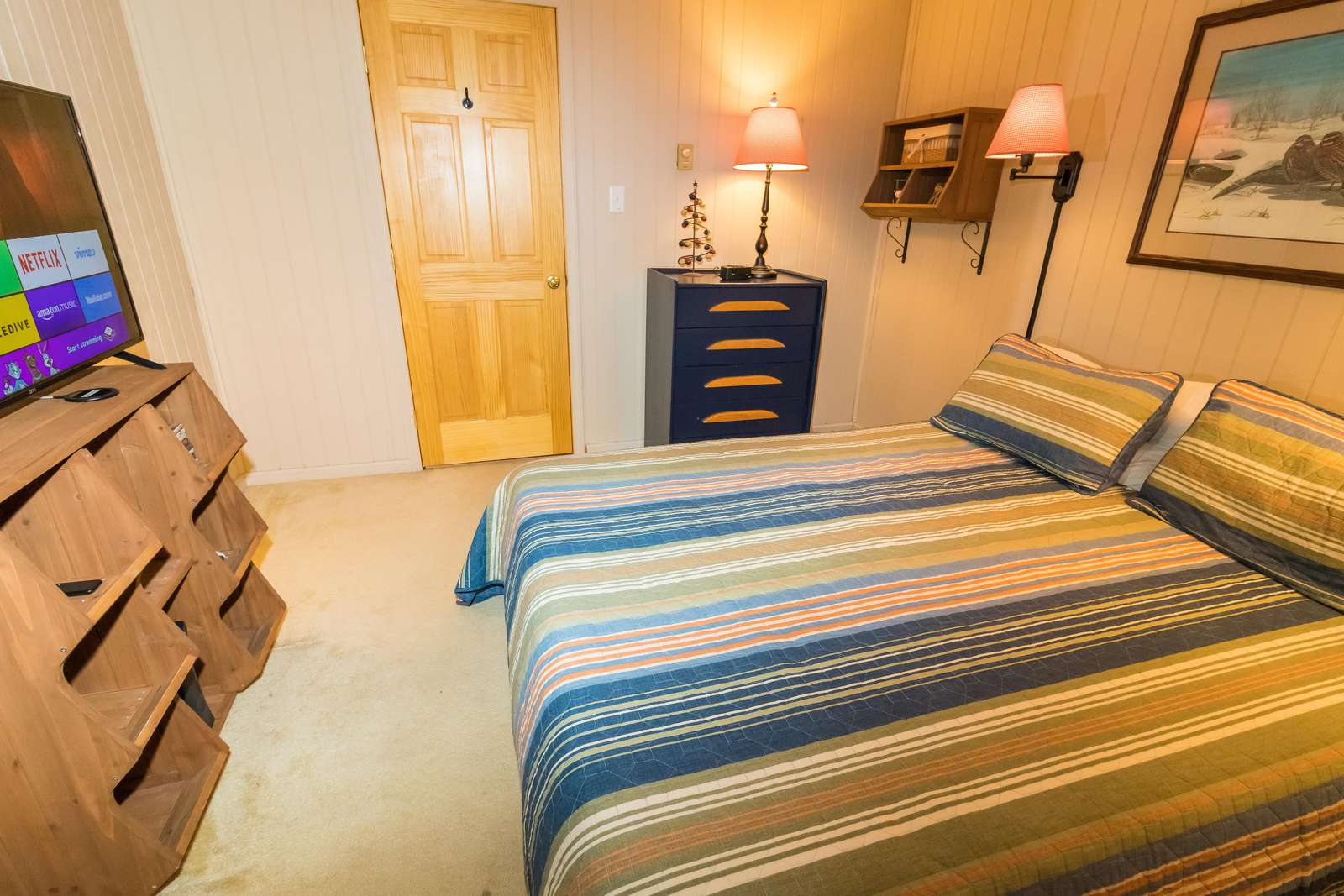 Full-sized bed in second bedroom; chest of drawers and closet for storage.