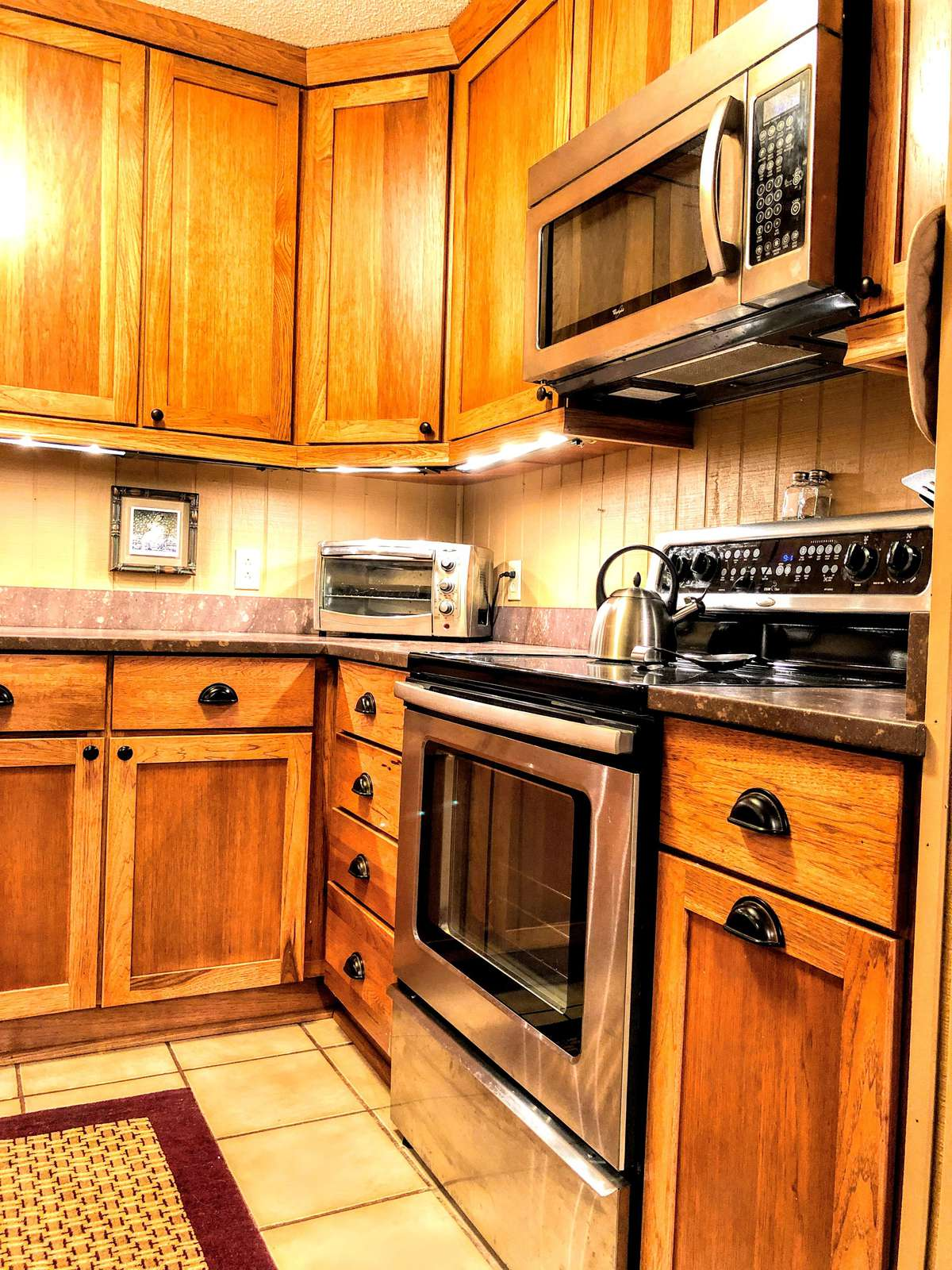 Fully-equipped kitchen (pots, pans, utensils, spices, cookware, etc.) with oak cabinets, solid-surface counter-tops, and stainless steel appliances!
