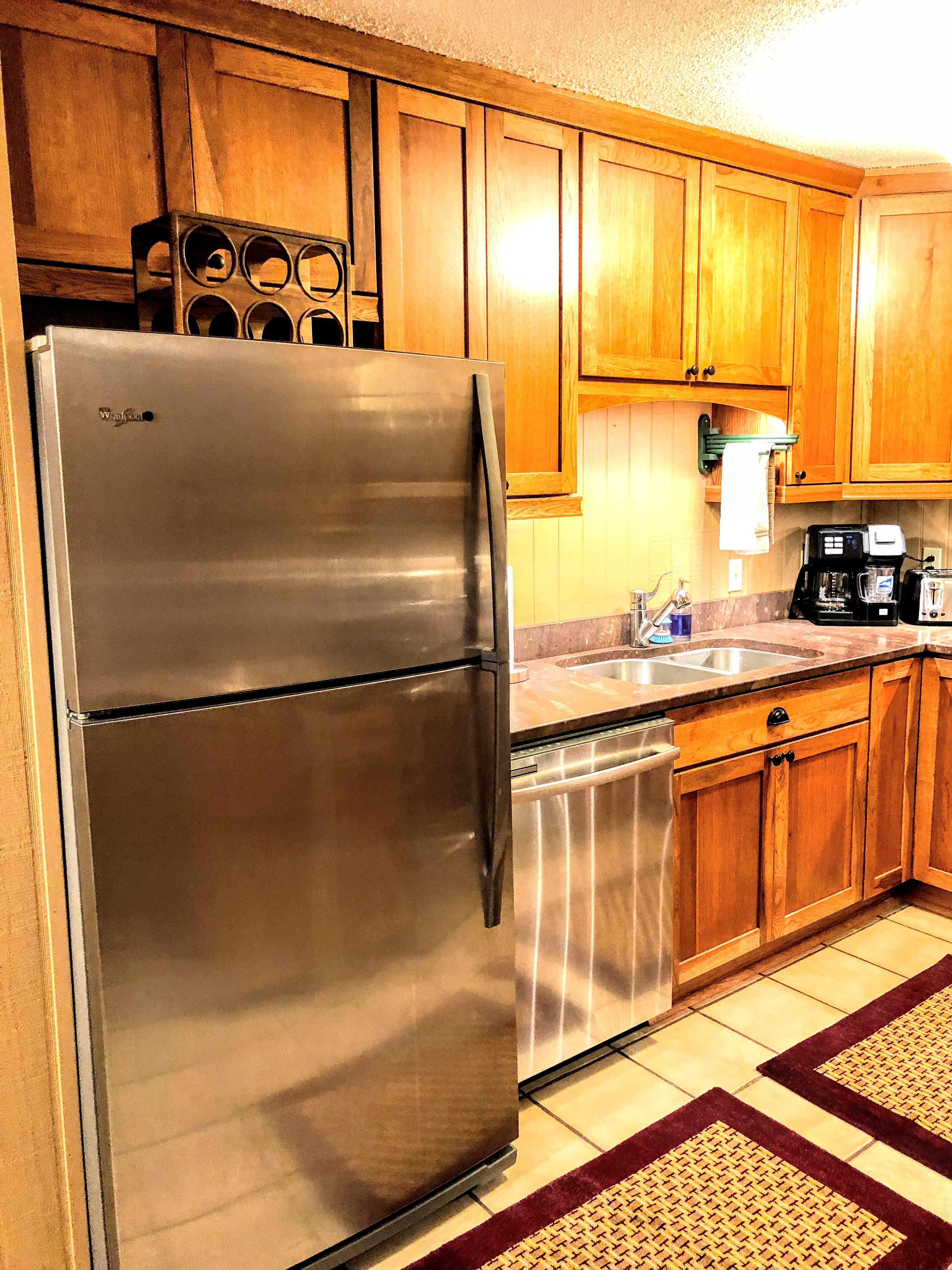 Full-sized stainless steel fridge, full-sized oven and electric cook top, toaster oven, and dishwasher